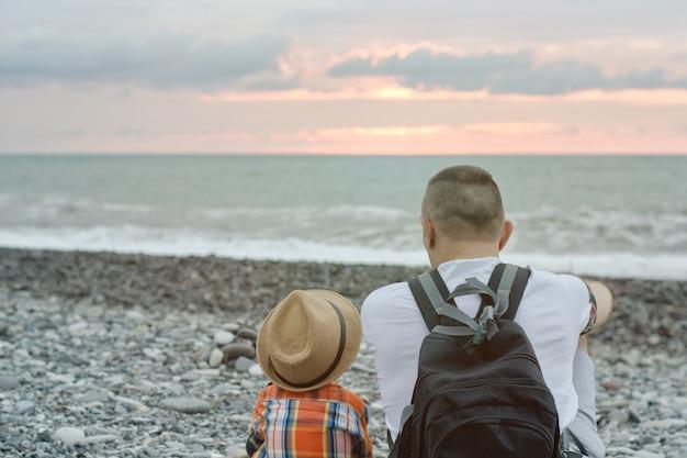 若い父と息子は、ビーチに座っています。