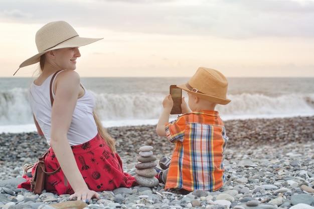 子供は母親を電話で、海の海岸で撮影します