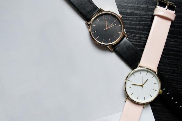 Две часы черного и розового цвета, без цифр на черном столе. светлая бумага, место для вашего текста