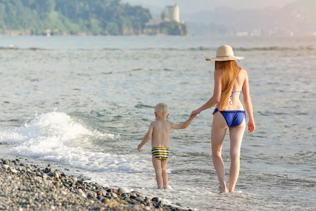 ママと彼の幼い息子は海沿いを歩いています。