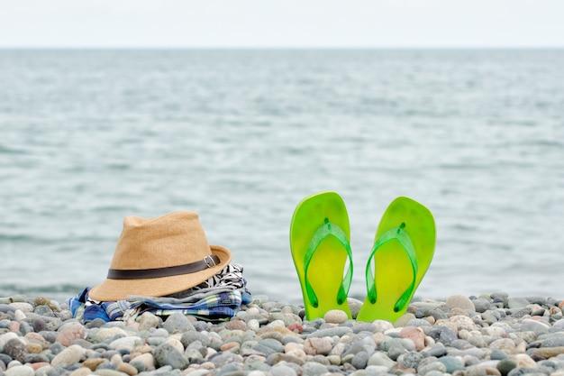小石のビーチで帽子、ウェア、ビーチサンダル。