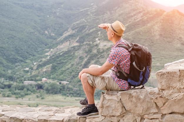 Молодой человек в шляпе с рюкзаком сидит на каменной стене на фоне зеленых гор и смотрит вдаль