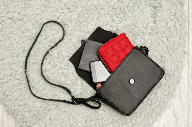 黒のハンドバッグ、赤い財布、携帯電話、口紅を開けます。灰色の毛皮の背景、トップビュー