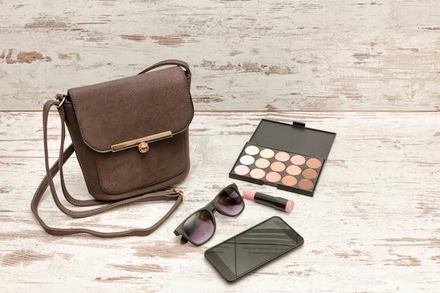 小さな茶色の女性のハンドバッグ、サングラス、スマートフォン、アイシャドウパレット、口紅