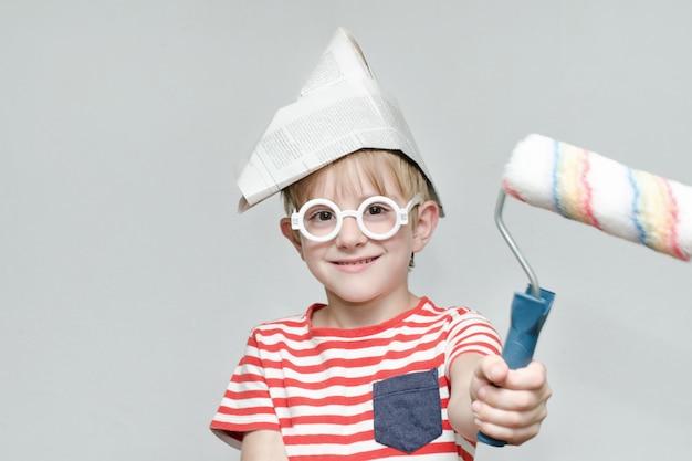 Мальчик в бумажной шапке играет в живописца портрет ролик для рисования