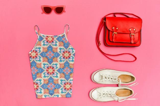 飾りのトップ、赤いハンドバッグ、白いスニーカー、バラ色のメガネ明るいピンクの背景、クローズアップ