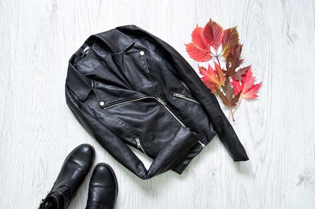 黒い革のジャケット、黒い靴、赤い葉