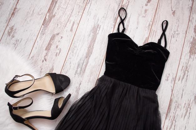 黒のイブニングドレスと木製の背景に靴