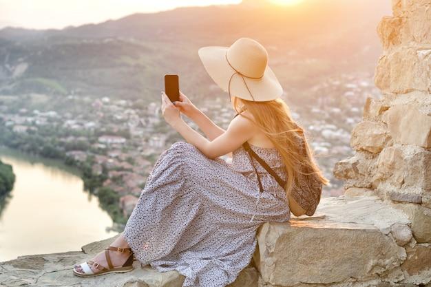 バックパックと帽子の美しい少女は、川と下の街の写真を撮る