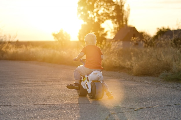 おもちゃの自転車の少年は、道路に乗っています。