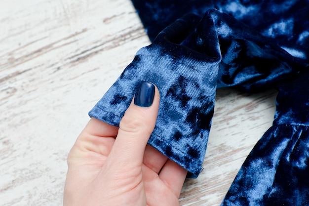 Рукав синего бархатного платья в женской руке. модно.