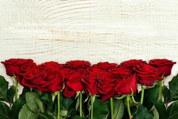 明るい木製の背景、上面に赤いバラ