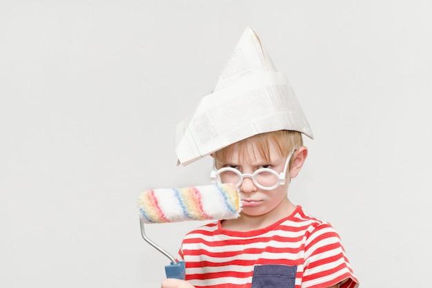 Мальчик в бумажной шляпе играет в художника. портрет. ролик для покраски