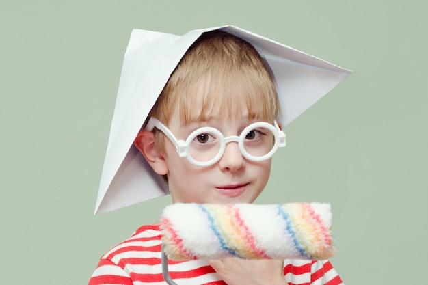 Мальчик в бумажной шляпе и очках играет художника. портрет. ролик для покраски