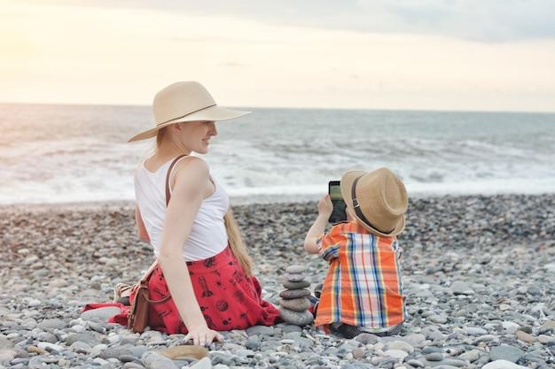 子供は海の海岸で電話で母親を撮影します