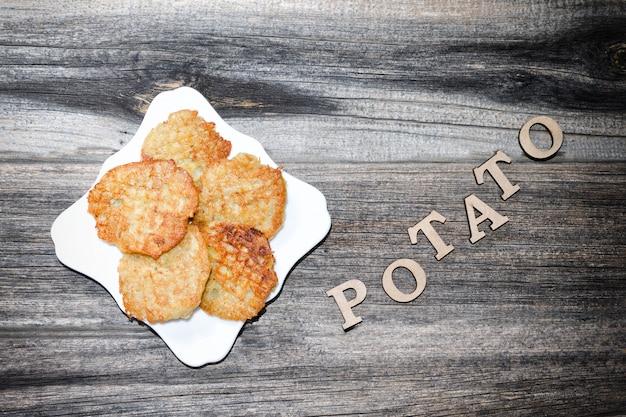 ジャガイモのパンケーキと碑文ジャガイモのプレート。灰色の木製、トップビュー