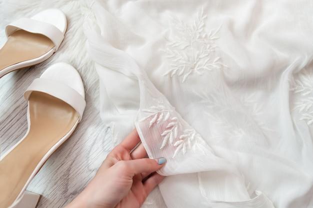 Белая прозрачная ткань в женской руке. белая обувь. фешенебельный