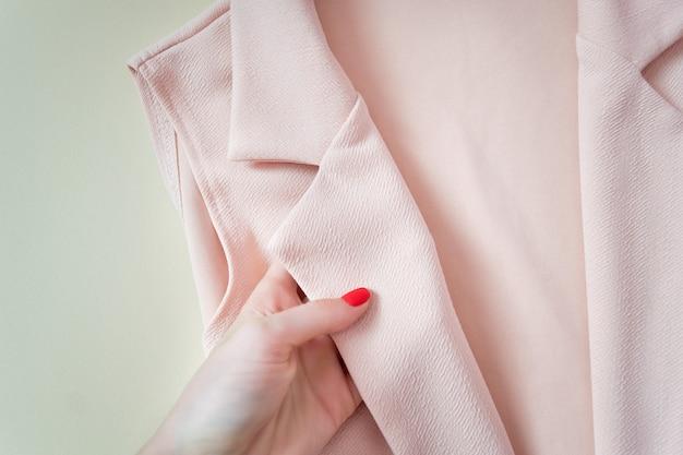 Розовый воротничок в женской руке. подробности. фешенебельный