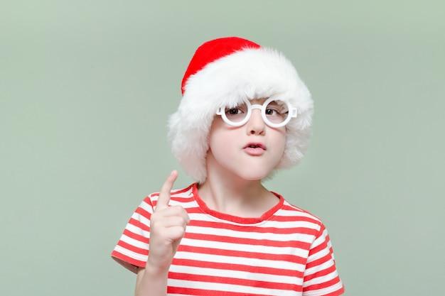 サンタの帽子とメガネで不機嫌そうな少年は指で脅す