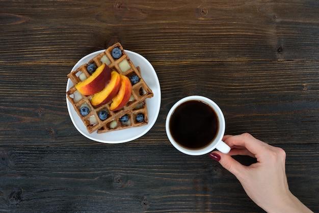 Бельгийские вафли с фруктами и ягодами. женская рука с чашкой кофе. вид сверху