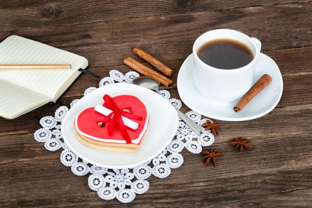 Чашка кофе, печенье в форме сердца и кофейники