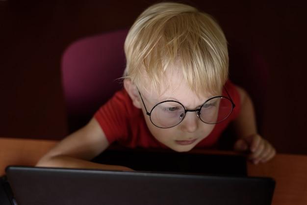 ラップトップを使用して眼鏡の深刻な金髪の少年の肖像画