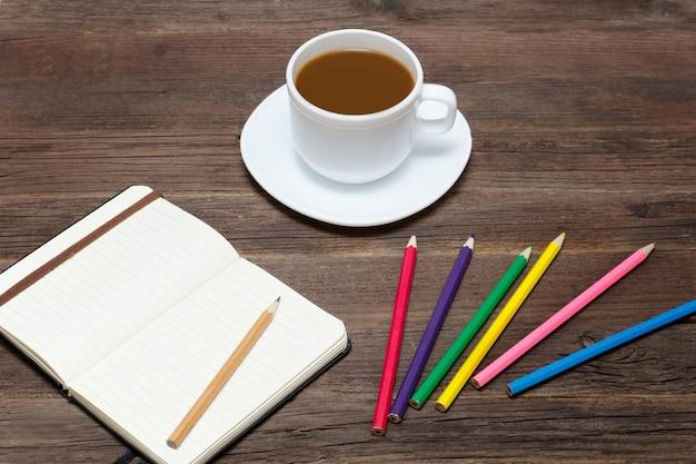 コーヒーマグ、色鉛筆、ノート。木製の背景