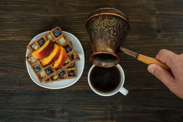 Бельгийские вафли с фруктами и ягодами. мужская рука наливает кофе из кофейника. вид сверху