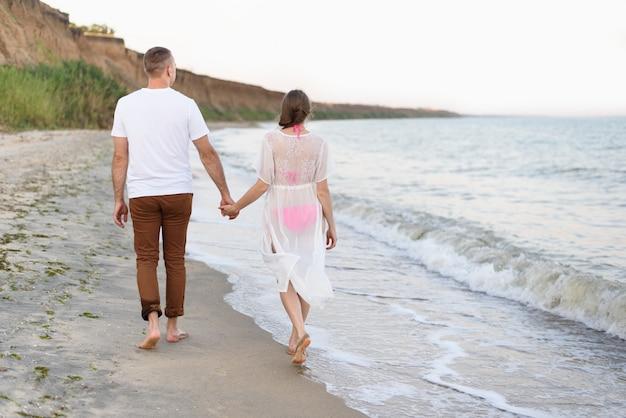 若いカップルは、海岸に沿って手を歩きます。背面図
