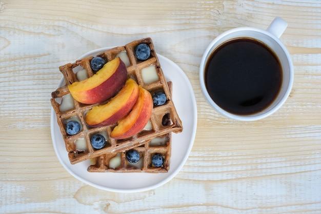 Шоколад бельгийские вафли с фруктами и чашка кофе на белом деревянном. вкусный завтрак. вид сверху