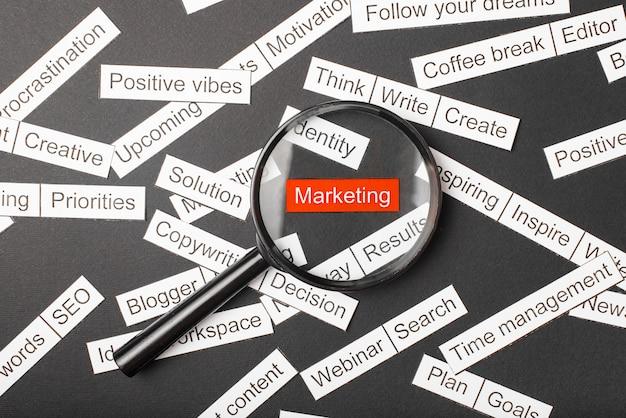 Стекло лупы над красной надписью маркетинга вырезать из бумаги. в окружении других надписей