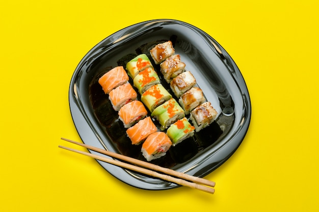 さまざまな寿司ロールの黒いプレート。上面図