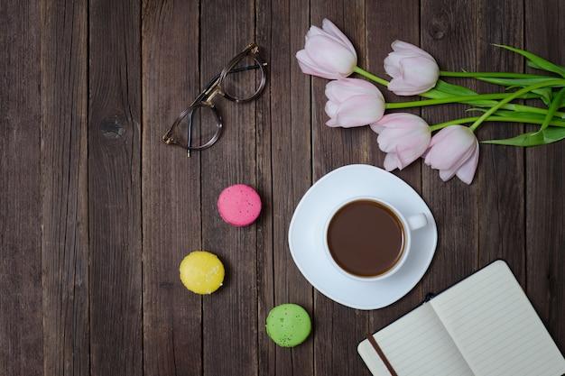 紅茶、マカロン、グラス、ピンクのチューリップ、ノートブックのトップビュー