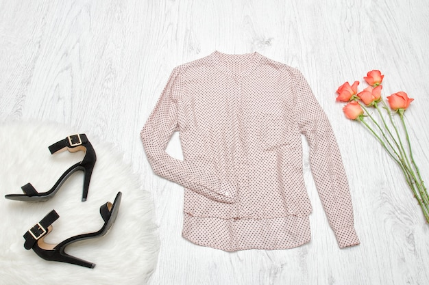 ベージュのブラウス、靴、バラのオレンジ。ファッショナブルなコンセプト