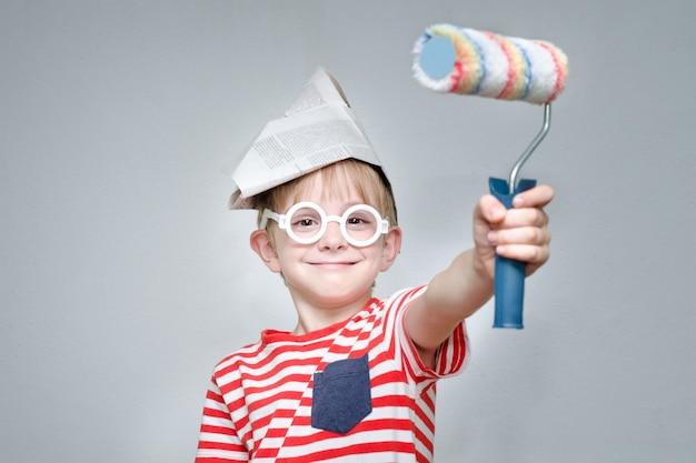 Мальчик в бумажной шляпе и очках. маленький художник. портрет. ролик для покраски