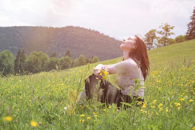 芝生に座っている野生の花の花束を持つかなり若い女性。の山。夏の晴れた日