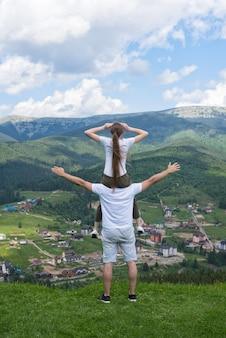 Девушка сидит на плечах парня и восхищается горами. вид сзади