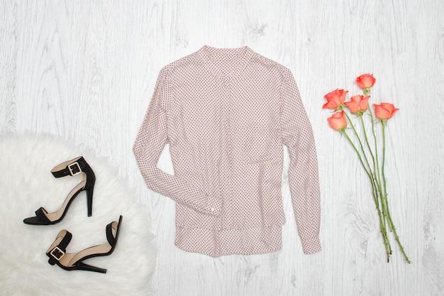 ベージュのブラウス、靴、バラのオレンジ