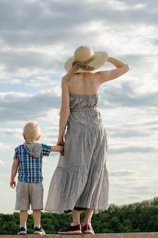 ママと息子は丘の上に立ち、空を背景に遠くを見ます