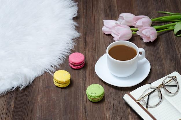 一杯のコーヒー、マカロン、グラス、ピンクのチューリップ、木の上のノートのトップビュー