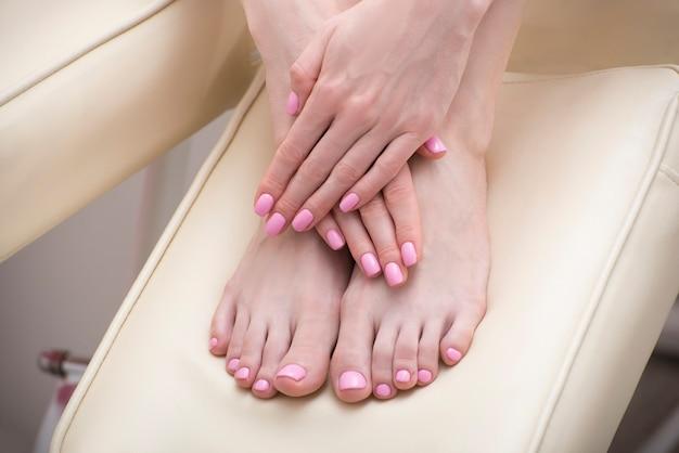 ピンクのマニキュアで女性の足と手。美容サロン。閉じる