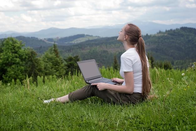 山の緑の草の上に座ってラップトップを持つ美しい夢を見る少女