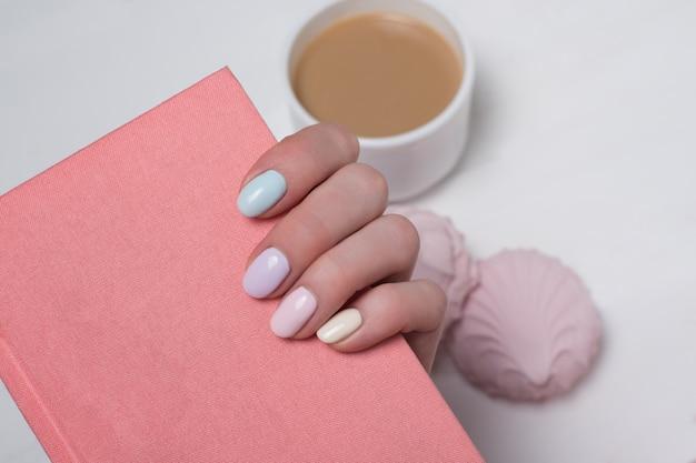 Розовый блокнот в женской руке. нежный маникюр. крупный план