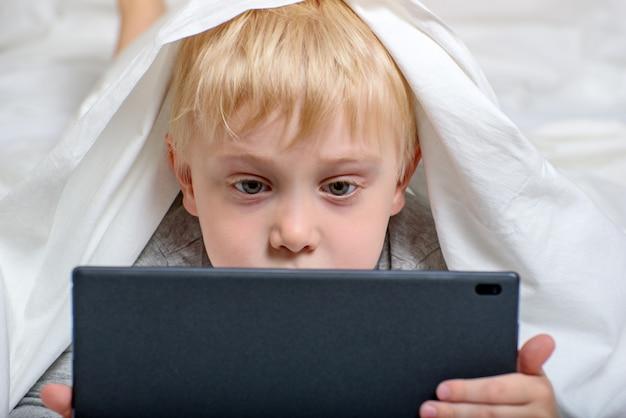金髪の少年は、タブレットで何かを見ています。ベッドに横になり、カバーの下に隠れます。ガジェットレジャー