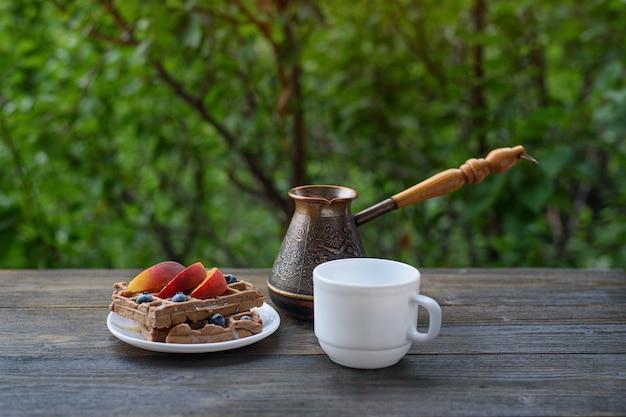Шоколад бельгийские вафли с фруктами, чашка кофе и джезве на зеленом. вкусный завтрак.