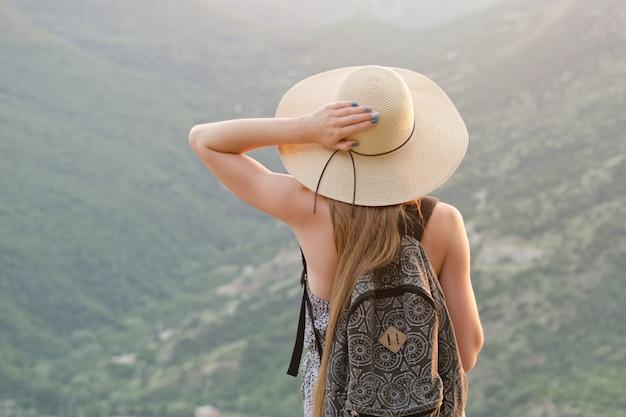 Красивая девушка с рюкзаком и широкой шляпкой стоит у зеленых гор
