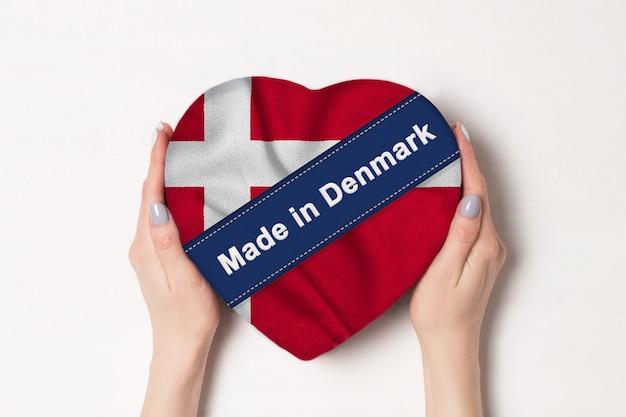 Надпись сделано в дании флаг дании. женские руки, держа коробку в форме сердца. ,