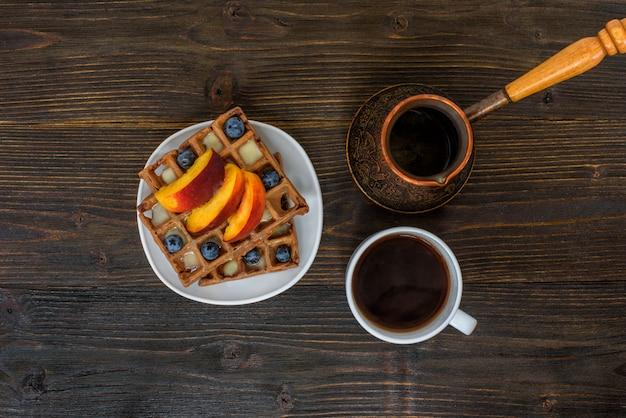 Шоколад бельгийские вафли с фруктами, чашка кофе и турка на деревянные. вкусный завтрак. вид сверху
