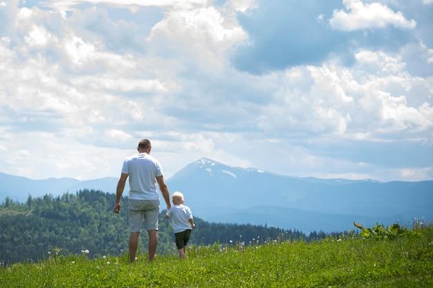 Отец и сын стоят на лужайке и любуются горами.