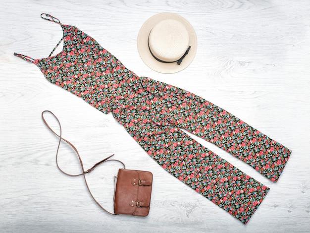 女性の夏のワードローブ。麦わら帽子、オーバーオール、ハンドバッグ。上面図